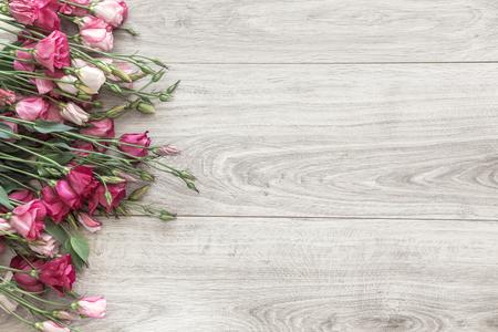 Roze Eustoma bloemen op natuurlijke houten vloer, selectieve aandacht, shabby chic stijl, ruimte voor aangepaste tekst.