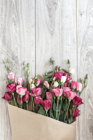Pink eustoma flowers wrapped in craft paper on natural wooden floor, selective focus, shabby chic style, space for custom text.