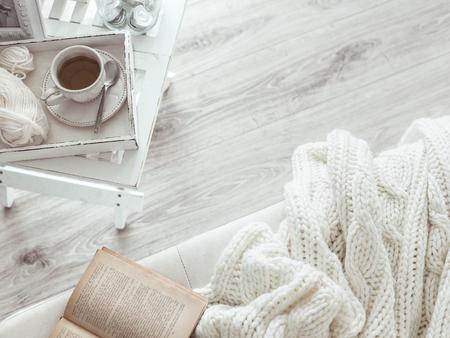 ropa de invierno: Todav�a detalles de la vida, una taza de t� en la bandeja de madera retro de la vendimia en una mesa de caf� en la sala de estar, la parte superior punto de vista. Fin de semana de invierno Lazy con un libro en el sof�. Foto de archivo