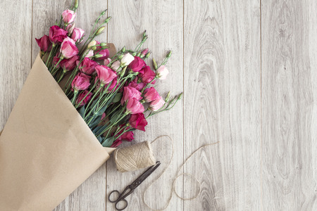 Pink eustoma flowers wrapped in craft paper, twine and vintage scissors on natural wooden floor, selective focus, shabby chic style, space for custom text. Stock Photo