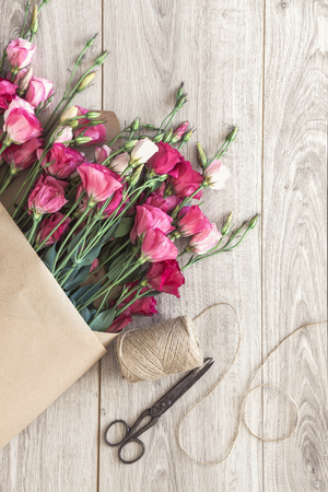 vintage paper: Pink eustoma flowers wrapped in craft paper, twine and vintage scissors on natural wooden floor, selective focus, shabby chic style, space for custom text. Stock Photo