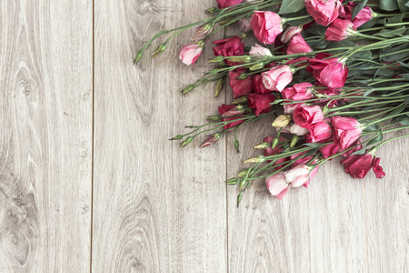 Pink eustoma flowers on natural wooden floor, selective focus, space for custom text.