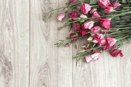 Roze eustoma bloemen op natuurlijke houten vloer, selectieve focus, ruimte voor aangepaste tekst.