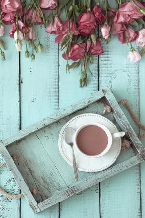 menta: Bandeja de madera de la vendimia con la taza de té de porcelana y flores de color rosa sobre fondo shabby menta elegante, alto punto de vista