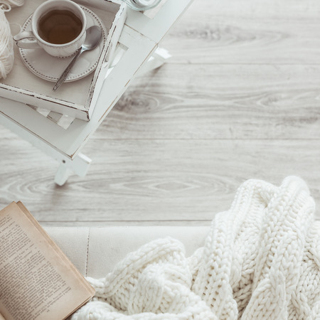 perezoso: Todav�a detalles de la vida, una taza de t� en la bandeja de madera retro de la vendimia en una mesa de caf� en la sala de estar, la parte superior punto de vista. Fin de semana de invierno Lazy con un libro en el sof�. Foto de archivo