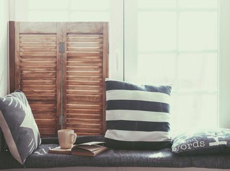 perezoso: Asiento de la ventana Cálido y acogedor, con cojines y un libro abierto, se iluminan a través de persianas vintage, decoración del hogar de estilo rústico.