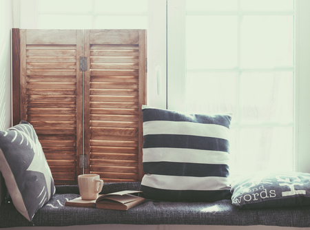relaxation: Warm and cozy window seat with cushions and a opened book, light through vintage shutters, rustic style home decor.