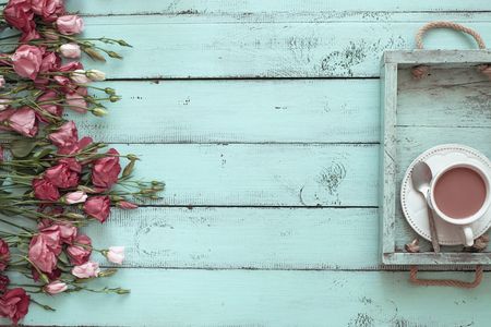 Vintage wooden tray with porcelain teacup and pink flowers on shabby chic mint background, top view point