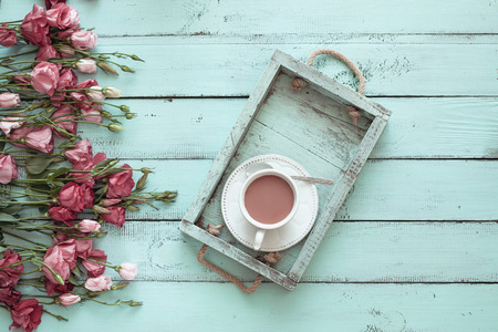 cottages: Vintage wooden tray with porcelain teacup and pink flowers on shabby chic mint background, top view point