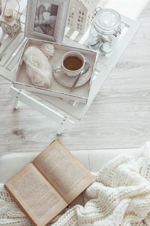 copa: Todavía detalles de la vida, una taza de té en la bandeja de madera retro de la vendimia en una mesa de café en la sala de estar, la parte superior punto de vista. Fin de semana de invierno Lazy con un libro en el sofá. Foto de archivo