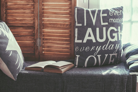 fin de semana: Asiento de la ventana Cálido y acogedor, con cojines y un libro abierto, se iluminan a través de persianas vintage, decoración del hogar de estilo rústico.