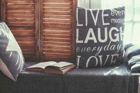 Warme en gezellige stoel bij het raam met kussens en een open boek, licht door vintage rolluiken, rustieke stijl interieur. Stockfoto