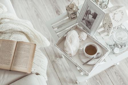 perezoso: Todavía detalles de la vida, una taza de té en la bandeja de madera retro de la vendimia en una mesa de café en la sala de estar, la parte superior punto de vista. Fin de semana de invierno Lazy con un libro en el sofá. Foto de archivo