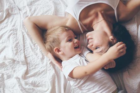 madre figlio: Giovane madre con il suo piccolo figlio di 2 anni in pigiama sono rilassanti e giocando nel letto durante il fine settimana insieme, mattina pigra, scena calda e accogliente. Colori pastello, messa a fuoco selettiva, vista superiore.