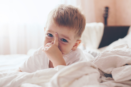 2 years old: 2 years old little boy dressed in pajamas are relaxing and playing in the parents bed, warm and cozy scene. Pastel colors, selective focus. Stock Photo
