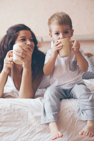 toddler boy: Young mother with her 2 years old little son dressed in pajamas are relaxing and playing in the bed at the weekend together, lazy morning, warm and cozy scene. Pastel colors, selective focus.