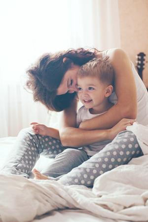 madre figlio: Giovane madre con il suo piccolo figlio di 2 anni in pigiama sono rilassanti e giocando nel letto durante il fine settimana insieme, mattina pigra, scena calda e accogliente. Colori pastello, messa a fuoco selettiva.