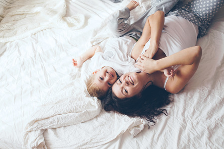 Young mother with her 2 years old little son dressed in pajamas are relaxing and playing in the bed at the weekend together, lazy morning, warm and cozy scene. Pastel colors, selective focus, top view.