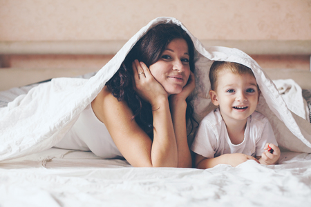 colores pastel: Joven madre con su 2 años de edad pequeño hijo en pijama son relajantes y jugando en la cama en el fin de semana juntos, mañana tranquila, cálida y acogedora escena. Colores pastel, enfoque selectivo. Foto de archivo