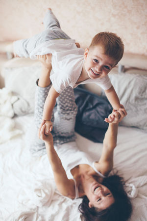 parents with baby: Young mother with her 2 years old little son dressed in pajamas are relaxing and playing in the bed at the weekend together, lazy morning, warm and cozy scene. Pastel colors, selective focus.