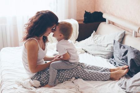 dois: Matriz nova com seu filho pequeno 2 anos de idade vestida de pijama são relaxantes e jogar na cama no fim de semana juntos, manhã preguiçosa, cena quente e aconchegante. Cores pastel, foco seletivo.