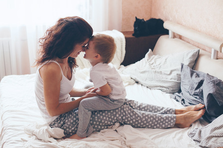 morning: Young mother with her 2 years old little son dressed in pajamas are relaxing and playing in the bed at the weekend together, lazy morning, warm and cozy scene. Pastel colors, selective focus.
