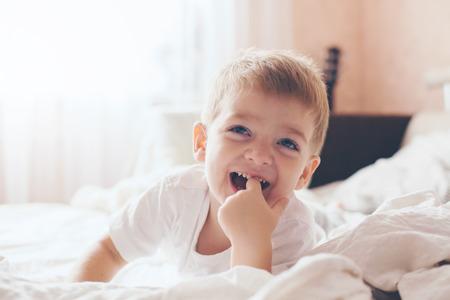 잠옷을 입고 2 세 어린 소년 휴식 및 부모의 침대, 따뜻하고 아늑한 장면에서 재생됩니다. 파스텔 색상, 선택적 포커스.