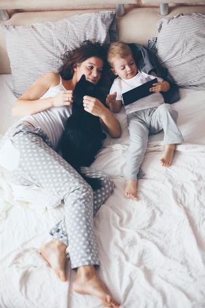 잠옷을 입고 그녀의 2 세 작은 아들과 함께 젊은 어머니는 편안하고, 따뜻하고 아늑한 장면을 함께 주말에 침대에서 재생 게으른 아침 있습니다. 파스