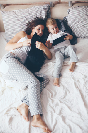 mama e hijo: Joven madre con su 2 años de edad pequeño hijo en pijama son relajantes y jugando en la cama en el fin de semana juntos, mañana tranquila, cálida y acogedora escena. Colores pastel, enfoque selectivo. Foto de archivo