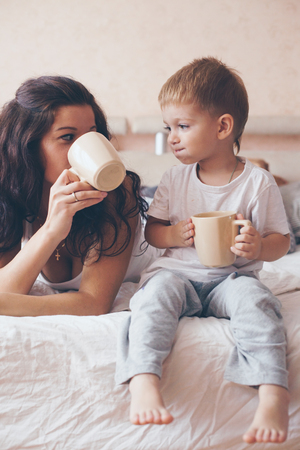 ni�os desayuno: Joven madre con su 2 a�os de edad peque�o hijo en pijama son relajantes y jugando en la cama en el fin de semana juntos, ma�ana tranquila, c�lida y acogedora escena. Colores pastel, enfoque selectivo. Foto de archivo