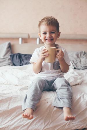 Die 2 Jahre alt kleinen Körper in Pyjamas gekleidet sind entspannend und trinken Milch im Bett, warme und gemütliche Szene. Pastellfarben, geringe Tiefenschärfe. Standard-Bild - 45930987