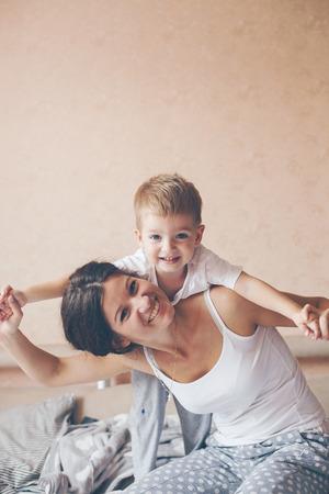 Joven madre con su 2 años de edad pequeño hijo en pijama son relajantes y jugando en la cama en el fin de semana juntos, mañana tranquila, cálida y acogedora escena. Colores pastel, enfoque selectivo. Foto de archivo - 45931061