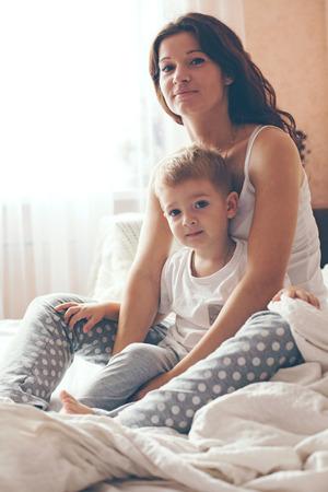 pijama: Joven madre con su 2 años de edad pequeño hijo en pijama son relajantes y jugando en la cama en el fin de semana juntos, mañana tranquila, cálida y acogedora escena. Colores pastel, enfoque selectivo. Foto de archivo