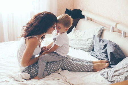 lazy: Young mother with her 2 years old little son dressed in pajamas are relaxing and playing in the bed at the weekend together, lazy morning, warm and cozy scene. Pastel colors, selective focus.