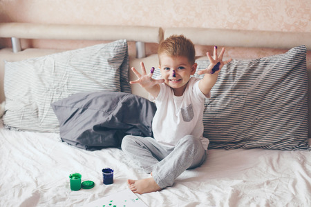 toddler: 2 years old little boy dressed in pajamas is painting in the bed