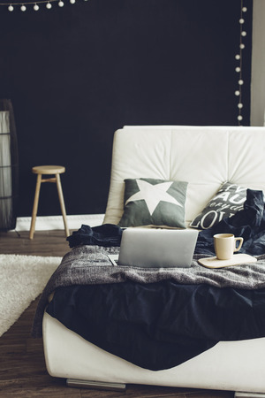 blanket: Cozy couch with blanket, coffee and laptop in modern interior in black and white colors Stock Photo