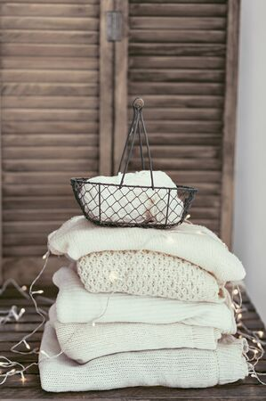 pastel colors: Knitwear closeup, stack of white sweaters on old rustic background, pastel colors.