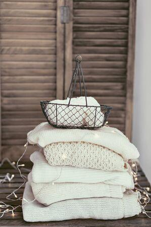colores pastel: Prendas de punto Primer plano, pila de suéteres blancos sobre fondo antiguo rústico, colores pastel.