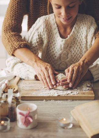 Mama con sus 9 años de edad hija están cocinando pastel de vacaciones en la cocina, la serie del estilo de vida de la foto, primer de las manos.