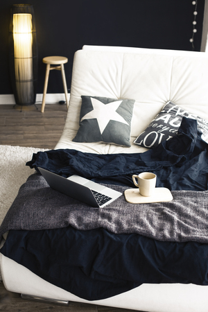 white interior: Cozy couch with blanket, coffee and laptop in modern interior in black and white colors Stock Photo