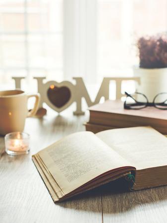 Sladký domov. Otevřená kniha s brýlemi, svíčkou a šálkem čaje na pozadí, selektivní zaměření. Text v knize není rozpoznatelný. Reklamní fotografie