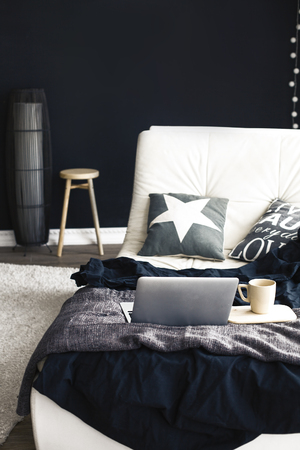 interior home: Cozy couch with blanket, coffee and laptop in modern interior in black and white colors Stock Photo