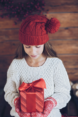 beautiful preteen girl: Child giving a Christmas present on rustic wooden background, farmhouse interior.