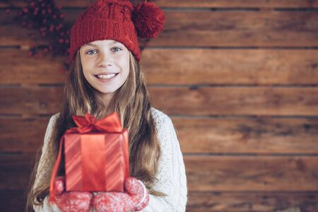 niños sonriendo: Niño que da un regalo de Navidad en el fondo de madera rústica, interior granja.