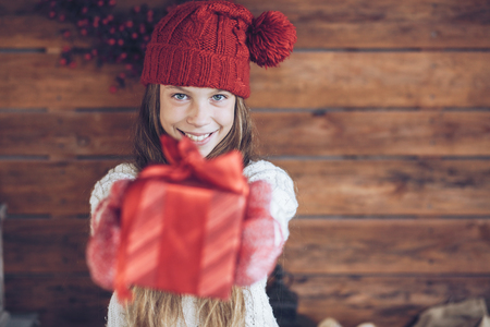 sweater girl: Child giving a Christmas present on rustic wooden background, farmhouse interior.