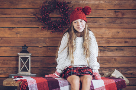 old barn in winter: Child sitting on a vintage bench on rustic wooden background, Christmas decorated farmhouse interior. Stock Photo