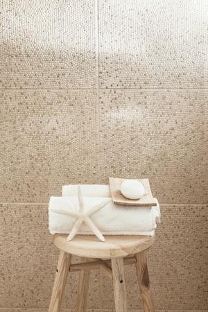 vida natural: Hotel decoración del baño cerca. Blanca toallas, jabón, esponja y estrellas de mar en el taburete de madera sobre losa de piedra. Colores naturales, la naturaleza muerta.