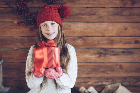 knit: Child giving a Christmas present on rustic wooden background, farmhouse interior.