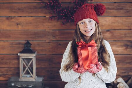 pullover: Child giving a Christmas present on rustic wooden background, farmhouse interior.