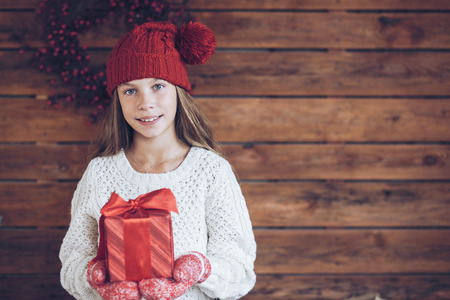 christmas hat: Child giving a Christmas present on rustic wooden background, farmhouse interior.